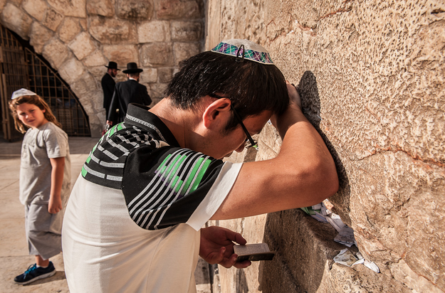 Gizzon prays by the Western Wall that draws the attention of a curious surrounder.